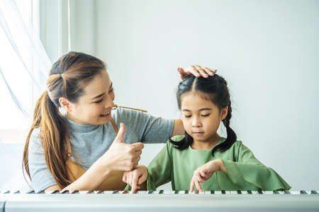 Foto de Happy family playing at home, The mother was delighted with the little daughter with a thumbs up to be able to play the piano. - Imagen libre de derechos
