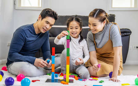 Photo pour Family and childhood concept. Young family spends time in playroom. Asian father, mother and daughter sitting on the floor and playing with colorful blocks - image libre de droit