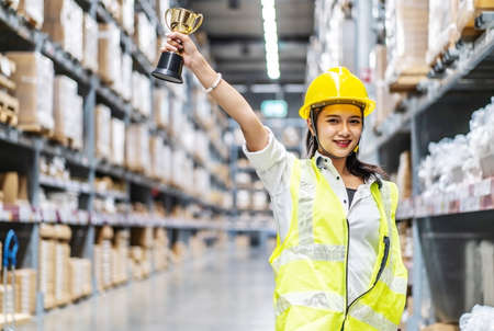 Photo for Happy woman warehouse worker holding a trophy after being selected as an outstanding employee - Royalty Free Image