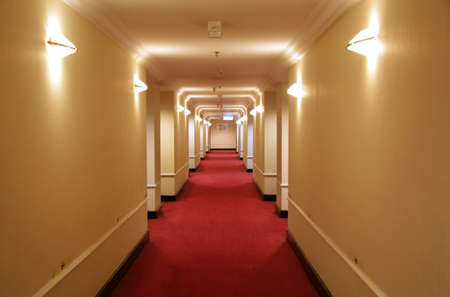Long hotel corridor with red carpet and yellow wallpaper
