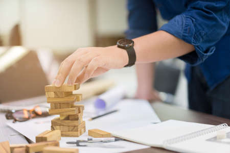 Photo pour close up engineering man hand playing wood block game for building tower in office room , success goal concept - image libre de droit