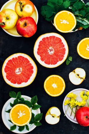 Mixed festive colorful tropical and citrus fruit sliced over black table top.