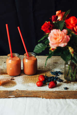 Hands makes strawberry smoothies in wooden table . Fresh strawberry smoothies fruit. Recipe carrot-strawberry smoothie. Action. Rustic dark style. Clean eating breakfast concept.