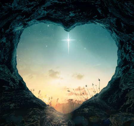 Foto de Good Friday concept: The cross of star with heart shape of empty tomb on night background - Imagen libre de derechos