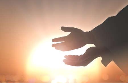 Photo pour Ascension day concept: Silhouette hands of God over blurred autumn sunset background - image libre de droit