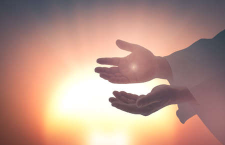 Foto de Easter Sunday concept: Silhouette scars in hands ofJesus Christ on sunrise background - Imagen libre de derechos