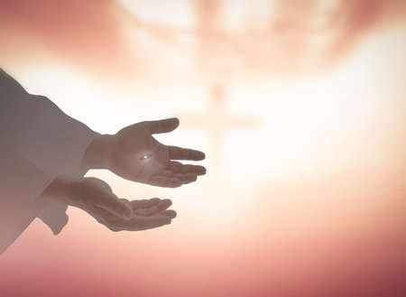 Photo pour Ascension day concept: Jesus Christ hands showing scars for Thomas over blurred cross sunset background - image libre de droit