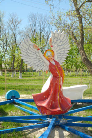 The statue of a girl in a long Russian folk sarafan dress hands like wings open and on the head kokoshnik in the form of a big star stands in the center of the children's carousel.