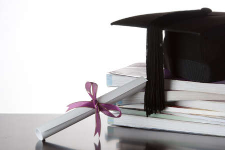 graduate certificate and graduate cap on a stack of books isolated on white