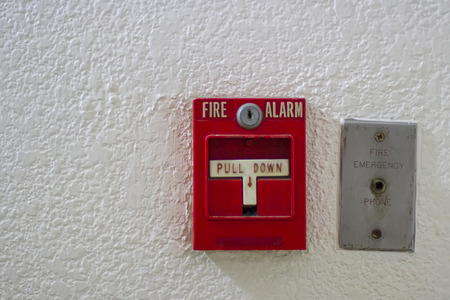 Red antique fire alarm button with white wall
