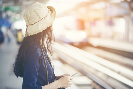 Photo pour Asian girl waiting train at skytrain station for travel in the big city, lifestyle and transportation concept - image libre de droit