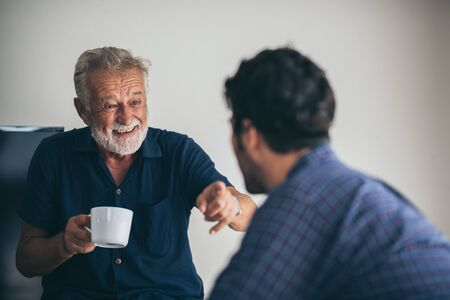 Photo pour Father-son bonding. Cheerful young man drinking coffee together with him - image libre de droit