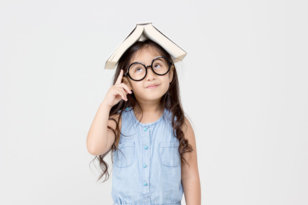 Portrait of little Asian child thinking and put a book on topの写真素材