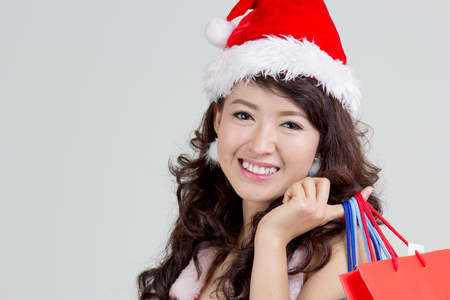 Close up Asian woman with santa dress holding colorful shopping bagsの写真素材