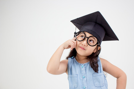 Happy Asian school kid graduate thinking with graduation cap