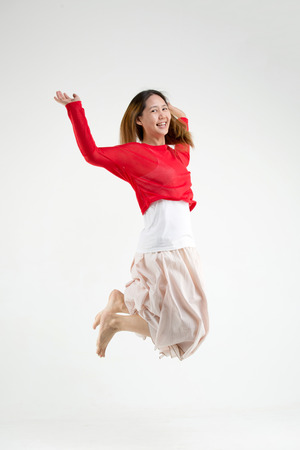 Happy Asian woman jumping in the airの写真素材