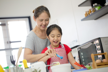 Photo for Little Asian cute chef cooking a bakery in kitchen with mother - Royalty Free Image