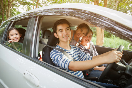 Foto de Happy Asian family on mini van are smiling and driving for travel on vacation - Imagen libre de derechos