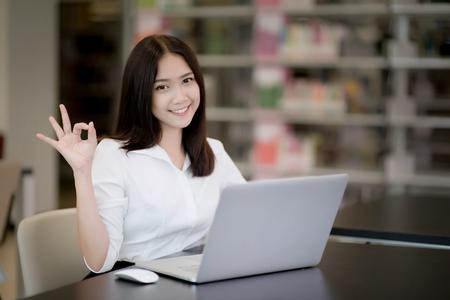 Foto de Portrait of a happy beautiful Asian young woman using laptop in office - Imagen libre de derechos