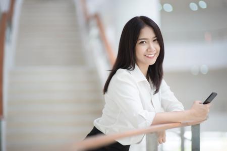 Foto de Young Asian woman executive working with a mobile phone in office building - Imagen libre de derechos