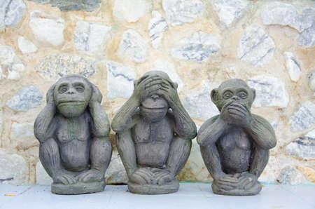 Three wise monkeys with stone background