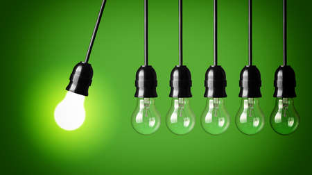 Idea concept on green background  Perpetual motion with light bulbs