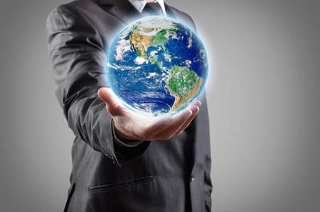 Businessman holds earth in a hand の写真素材