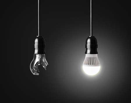 Photo for Broken light bulb and  glowing LED bulb on black - Royalty Free Image