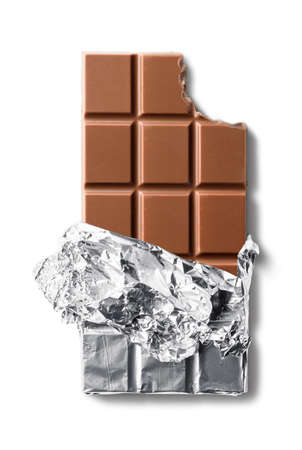 Top view of bitten milk chocolate bar in foil. Isolated on white background