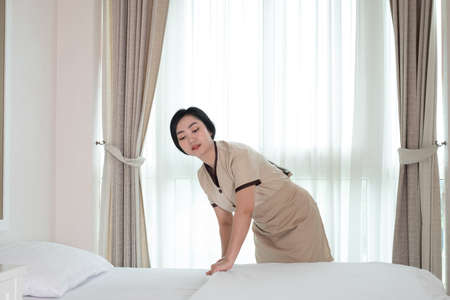 Photo pour Young beautiful Asia maid arranging blanket on the bed in hotel room - image libre de droit