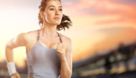 Foto de girl in sport on the sunset background - Imagen libre de derechos