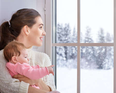 Happy cheerful family. Mother and baby hugging near window.