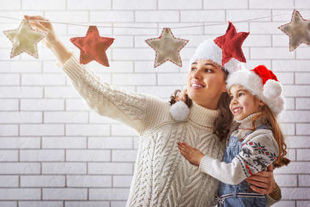 Merry Christmas! Happy mother and daughter hang a Christmas garland.の写真素材