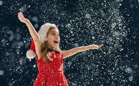 Photo for a Christmas miracle! happy little girl catching snowflakes in her hands - Royalty Free Image