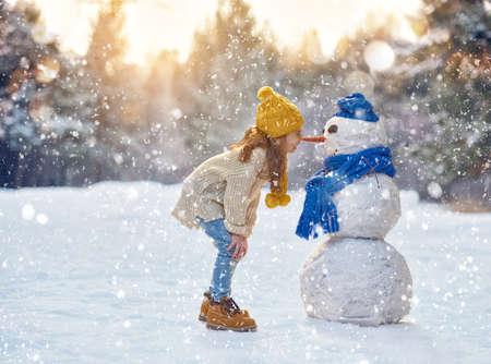 Photo pour happy child girl plaing with a snowman on a snowy winter walk - image libre de droit