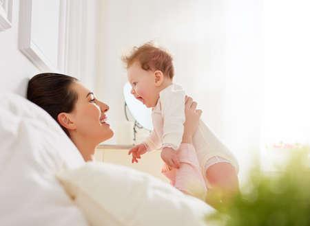 Foto de happy family. mother playing with her baby in the bedroom. - Imagen libre de derechos