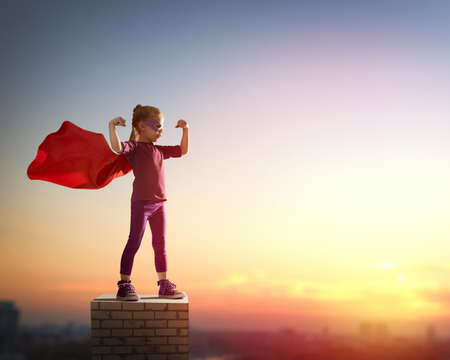 Foto per Little child girl plays superhero. Child on the background of sunset sky. Girl power concept - Immagine Royalty Free
