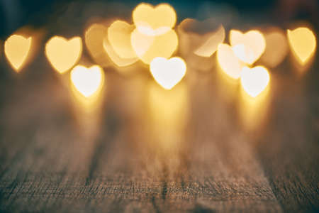Foto de Garland lights on wooden rustic background. Valentine's day background with hearts. The concept of love and Valentine's day. - Imagen libre de derechos
