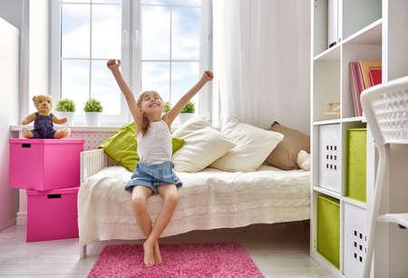 Foto de A nice child girl enjoys sunny morning. Good morning at home. Child girl wakes up from sleep. - Imagen libre de derechos