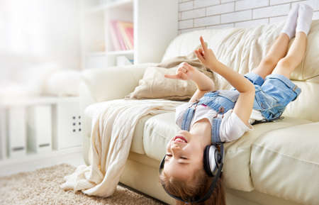 Photo pour little girl with headphones at home. child girl listening to music. - image libre de droit