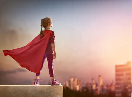 Foto de Little child girl plays superhero. Child on the background of sunset sky. Girl power concept - Imagen libre de derechos