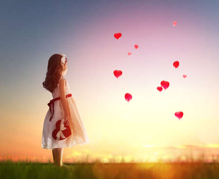 Photo pour Sweet child girl looking at red balloons. Balloons in shape of heart flying in the sunset sky. Wedding, Valentine, love concept. - image libre de droit