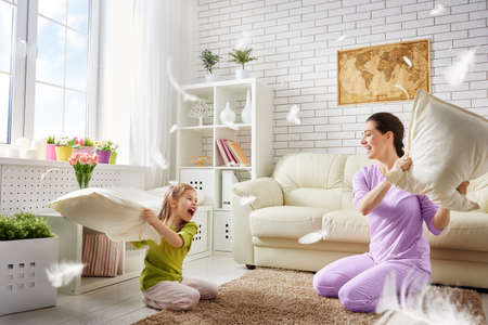 Foto de Happy family! The mother and her child girl are fighting pillows. Happy family games. - Imagen libre de derechos