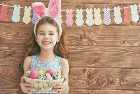 Photo for Cute little child girl wearing bunny ears on Easter day. Girl holding basket with painted eggs. - Royalty Free Image