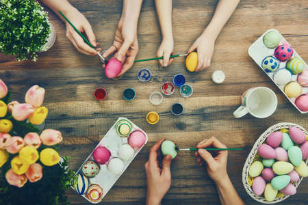 Foto de Happy easter! A mother, father and their daughter painting Easter eggs. Happy family preparing for Easter. - Imagen libre de derechos