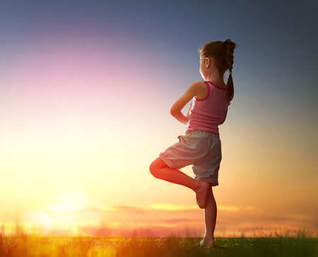 Photo pour Child girl in the Park. Yoga at sunset in the park. Girl is practicing yoga. - image libre de droit