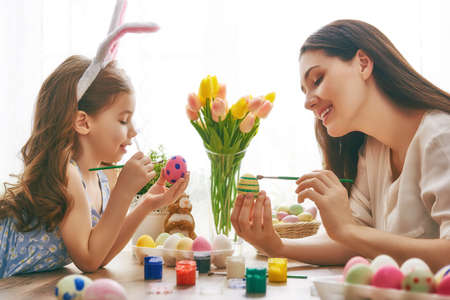 Foto de Happy easter! A mother and her daughter painting Easter eggs. Happy family preparing for Easter. Cute little child girl wearing bunny ears on Easter day. - Imagen libre de derechos