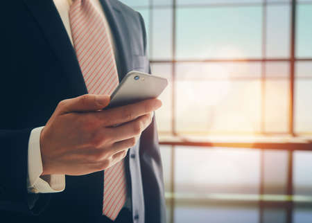 Photo pour Portrait of a confident man. Entrepreneur working on phone while standing in modern office interior. Intelligent male lawyer holding phone. - image libre de droit