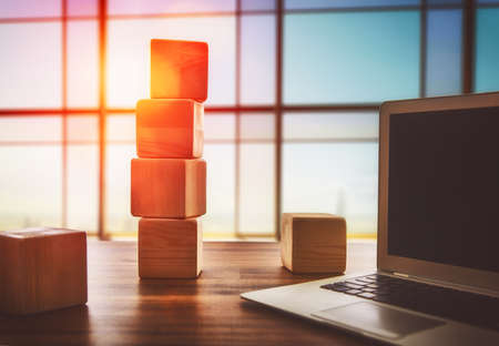 Photo pour The concept of planning in business. Wooden cubes and computer on a desk in the office. - image libre de droit