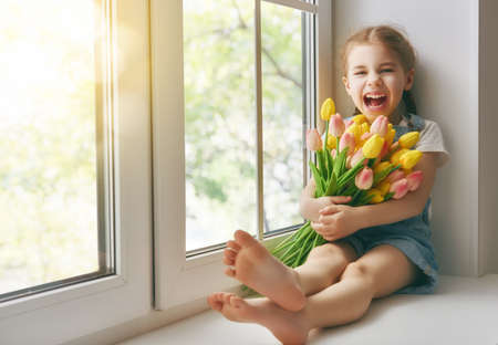Photo pour Adorable little child girl sitting on the window and holding tulips. Girl rejoices to spring and sun. - image libre de droit
